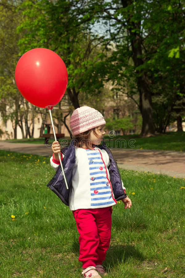 Little girl playing with balloon. Little girl playing with red balloon stock photo
