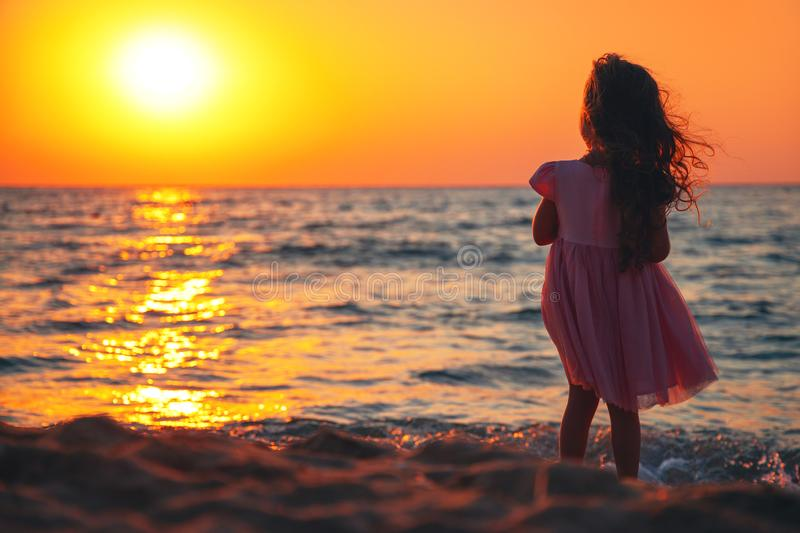 Little girl playing on the beach and enoying sunrise royalty free stock image