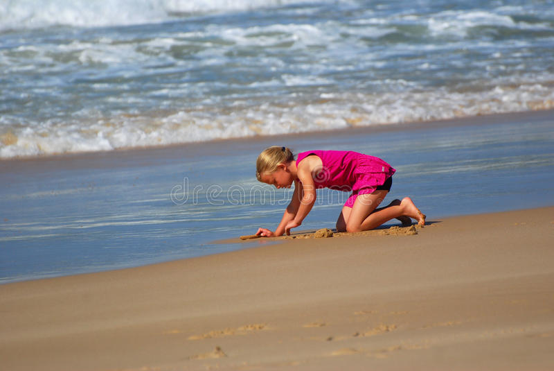 Little girl playing on beach. A cute little young Caucasian blond girl in a pink dress digging a hole in the sand, playing on the beach stock photo