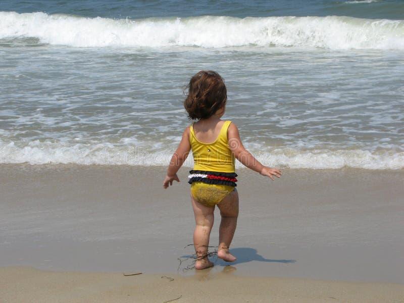 Little girl playing on beach stock photos