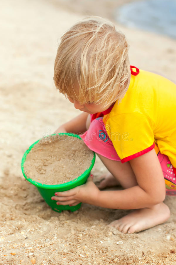 Little girl playing on a beach stock photos