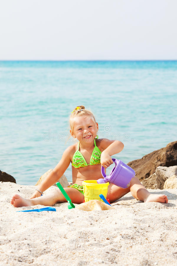 Little girl playing on the beach stock image