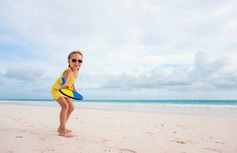 Little girl playing beach tennis royalty free stock photo