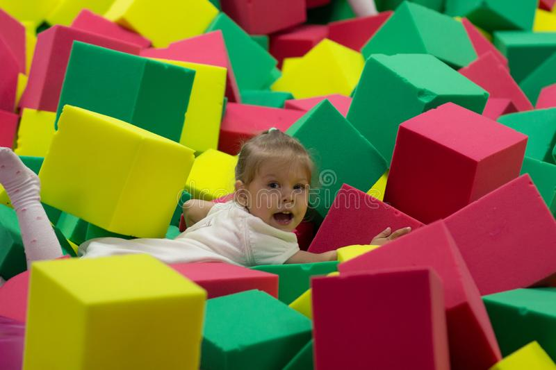 Little girl playing with big colorful foam rubber blocks royalty free stock photography