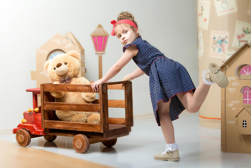 Little girl playing with a big wooden car. stock photo