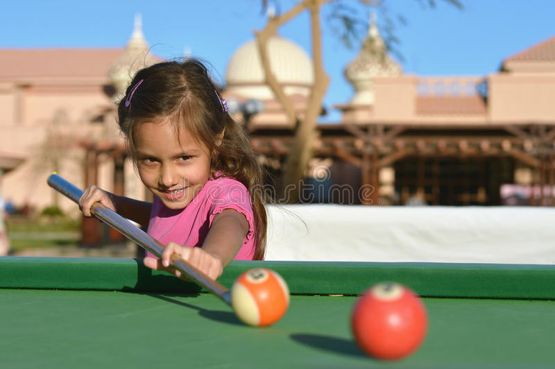 Little girl Playing billiards royalty free stock photos