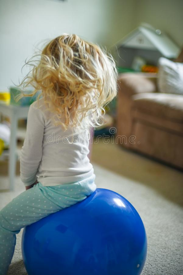 Little girl playing on bouncy ball royalty free stock photography