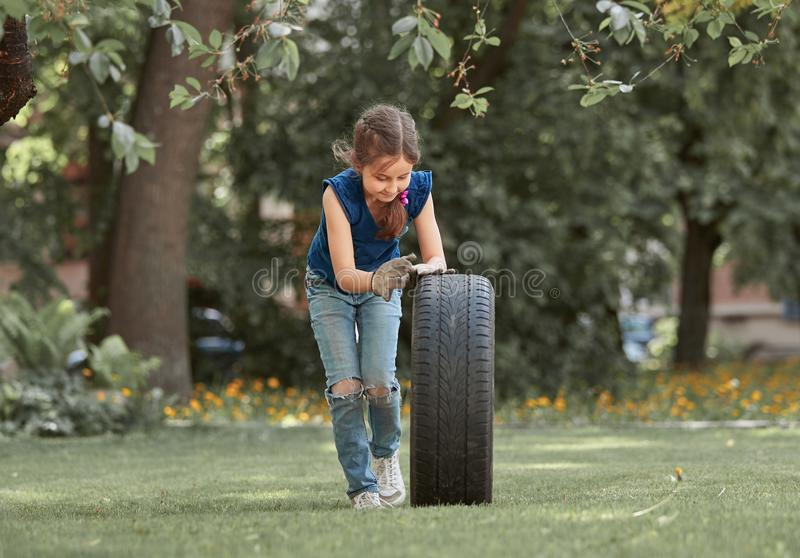 Little girl playing with a car tire on the Playground royalty free stock photography