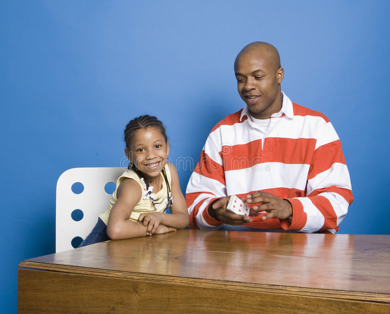Little girl playing cards with Dad. Man and daughter playing cards stock photos