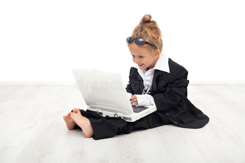 Little girl playing career woman role. Working on laptop dressed in large suit royalty free stock photography