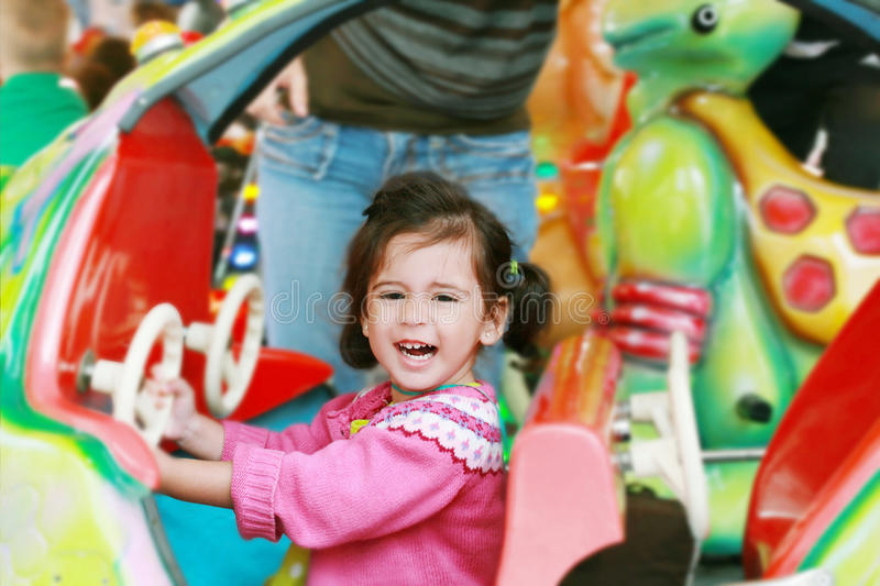 Little girl playing on carousel royalty free stock photos