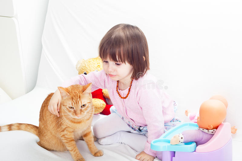 Little girl playing with cat. And baby dolls royalty free stock images