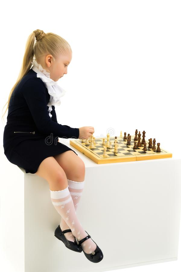 Little girl playing chess. Isolated on white background royalty free stock photo