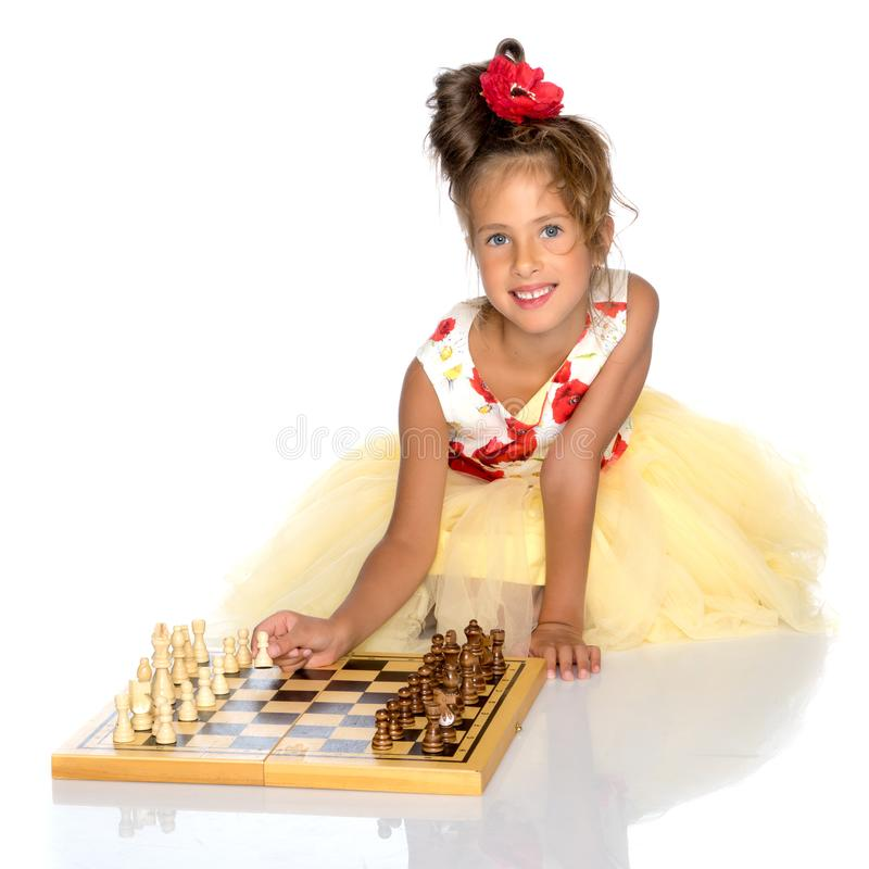 Little girl playing chess stock images