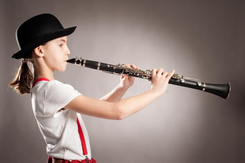Little girl playing clarinet stock photos