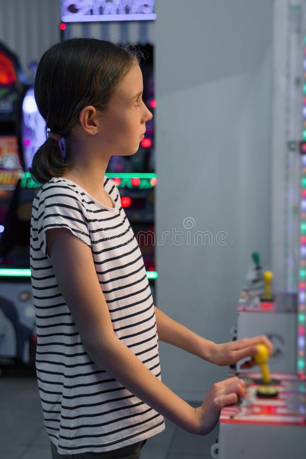 Little girl playing claw crane. royalty free stock photos
