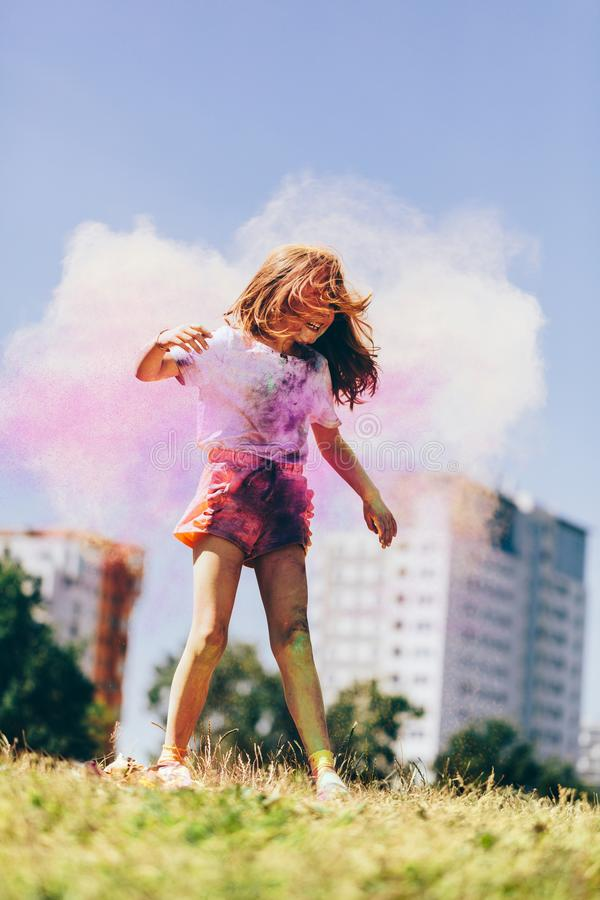 Little girl playing in colorful clouds of holi powder royalty free stock photography