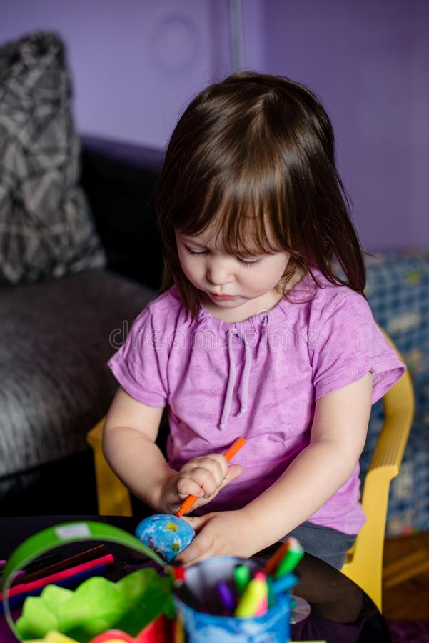 Little girl playing with crafts. Sitting in little yellow chair stock image