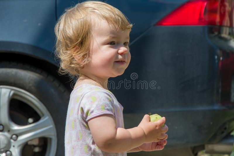 A little girl playing dangerously by the road, a child on the background of a passing car. A little girl playing dangerously by the road, a child on the stock photography