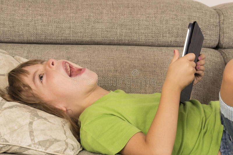 Little girl playing with a digital tablet royalty free stock image