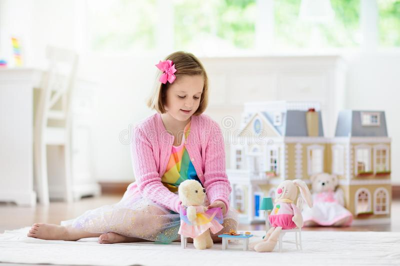 Little girl playing with doll house. Kid with toys royalty free stock images