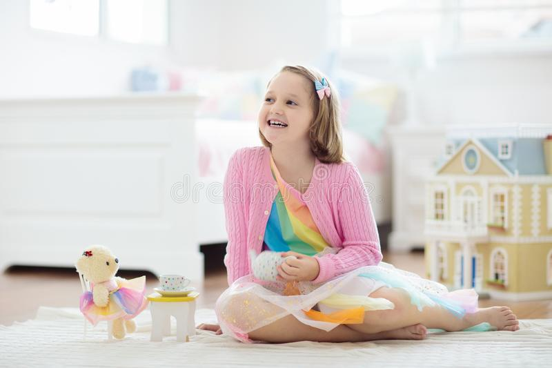 Little girl playing with doll house. Kid with toys royalty free stock image