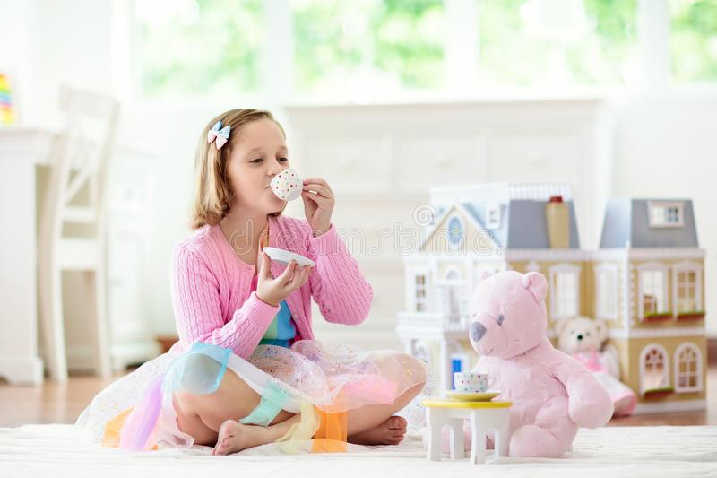 Little girl playing with doll house. Kid with toys stock images