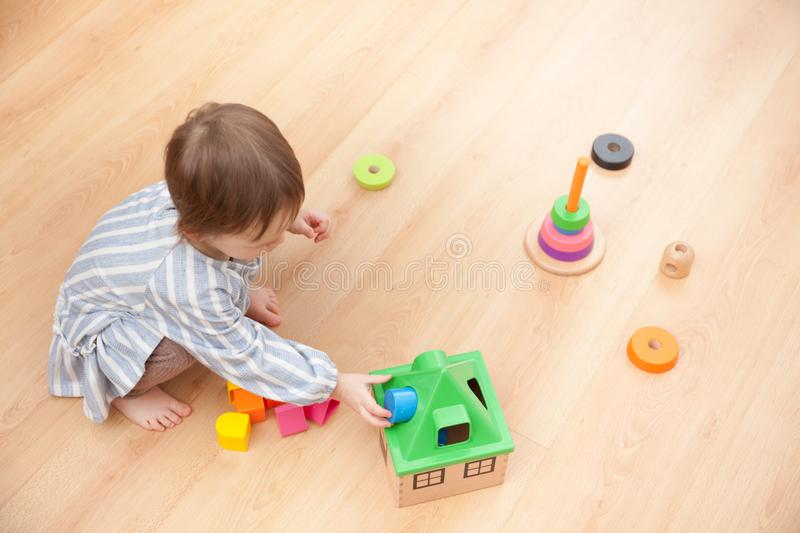 Little girl is playing with educational toys at home royalty free stock photos