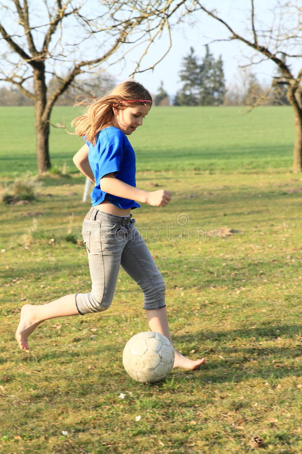 Little girl playing football barefoot royalty free stock photo