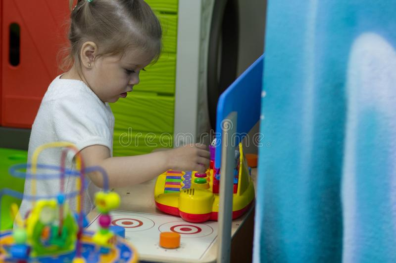 Little girl playing with toys in game room stock photo