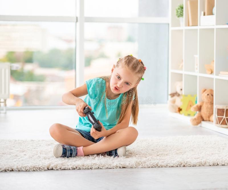 Little girl playing games with joystick. Sitting in her room stock photography