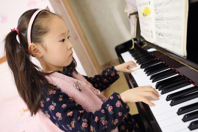 Little girl playing the piano at home royalty free stock photos