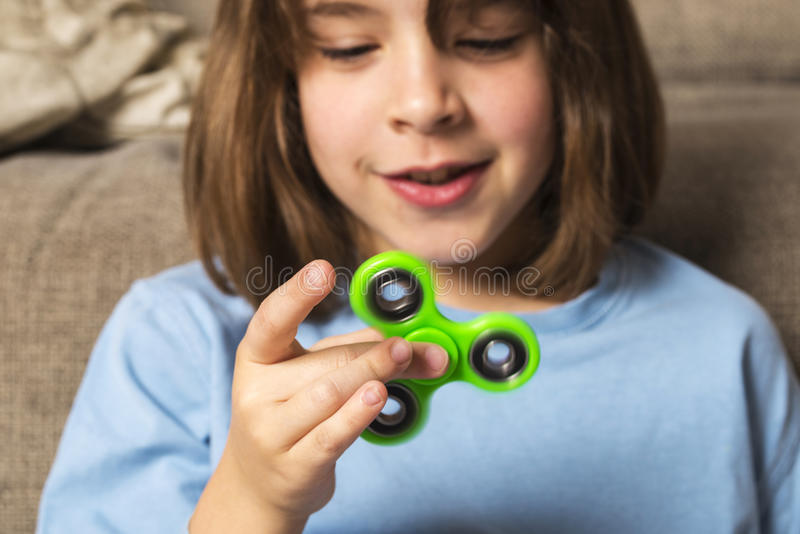 Little girl playing with green fidget spinner toy. To relieve stress at home stock photo
