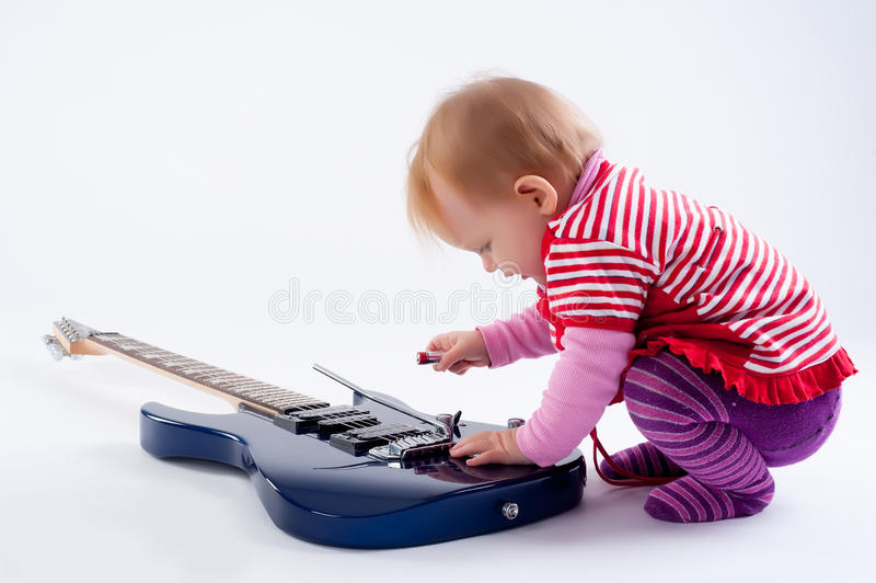 Little girl playing with guitar stock photography