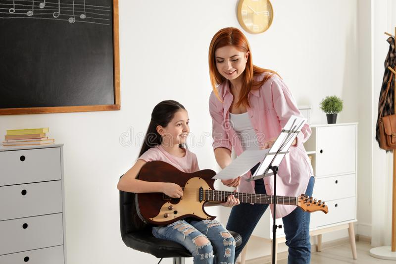 Little girl playing guitar with her teacher at music lesson stock image