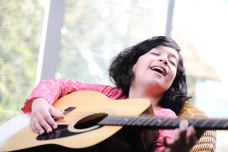Little girl playing guitar stock photography