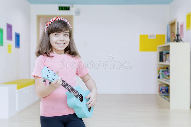 Little girl playing a guitar in the kindergarten stock image