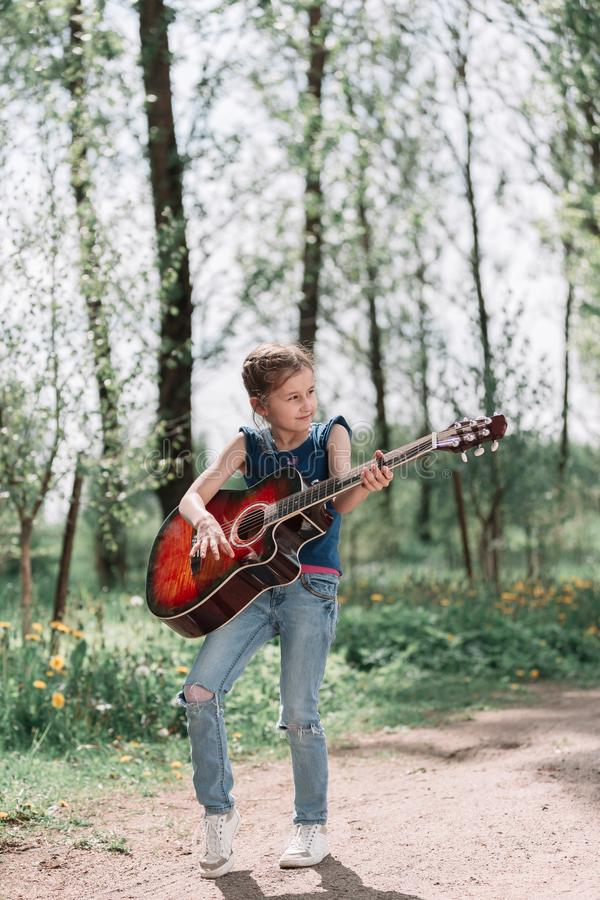 Little girl playing guitar standing on the path in the city Park royalty free stock photo