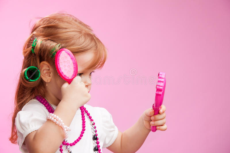 Little girl playing a hairdresser stock image