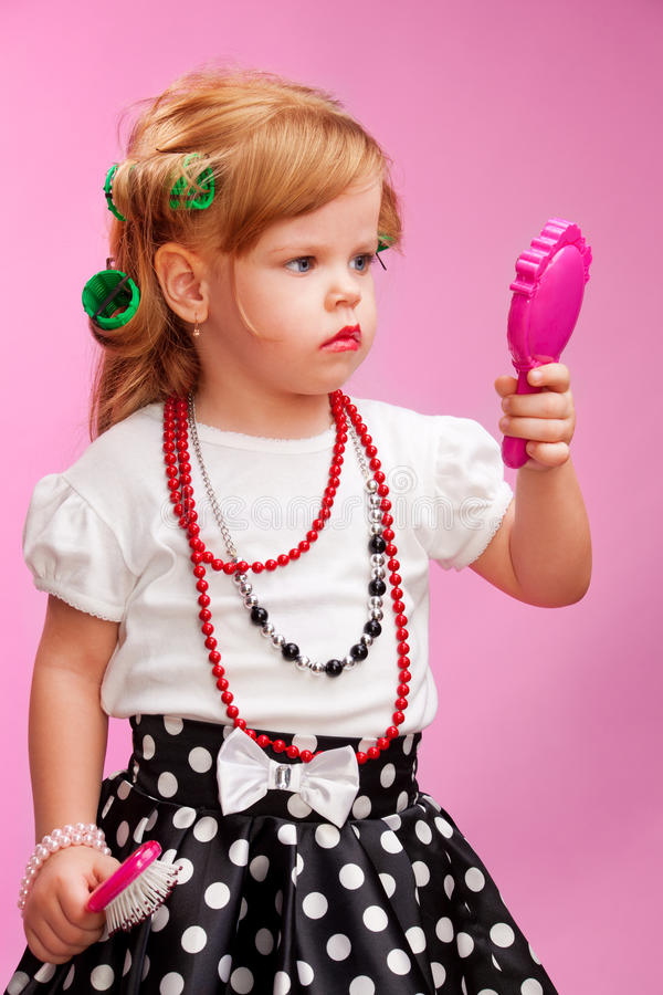 Little girl playing a hairdresser royalty free stock photography
