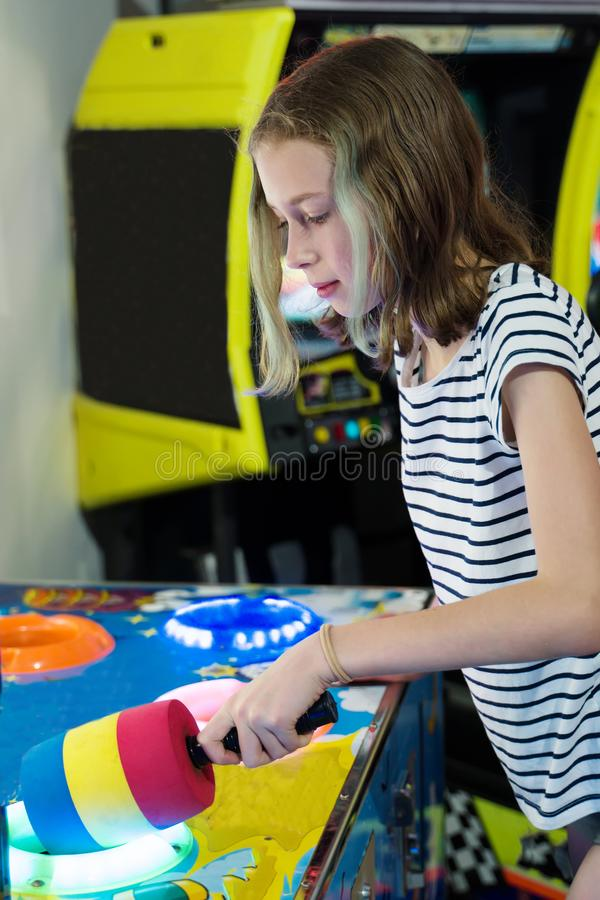 Little girl playing hammer arcade game. royalty free stock photography