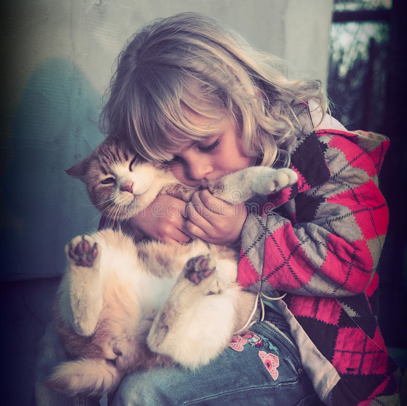 Little girl playing with her cat. Portrait of a blond little girl playing with her cat royalty free stock photos