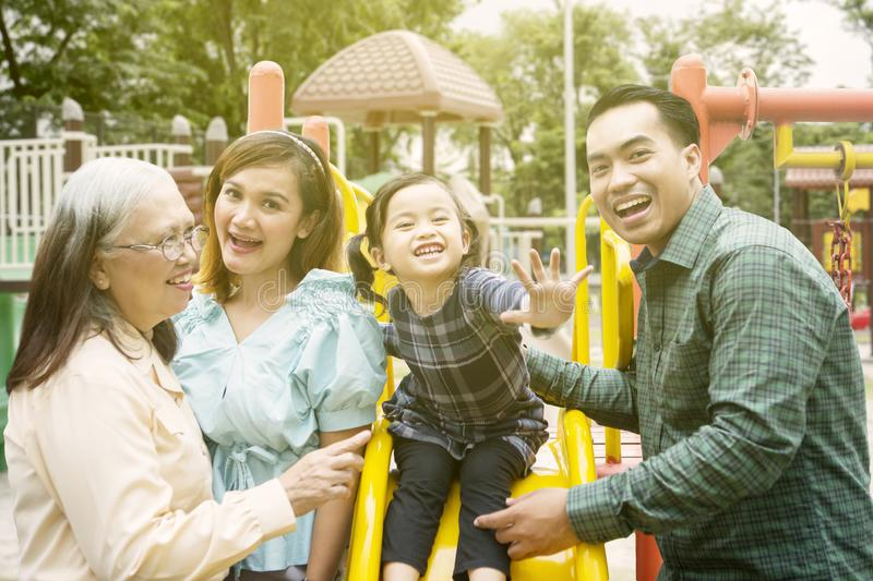 Little girl playing with her family in the playground stock photography