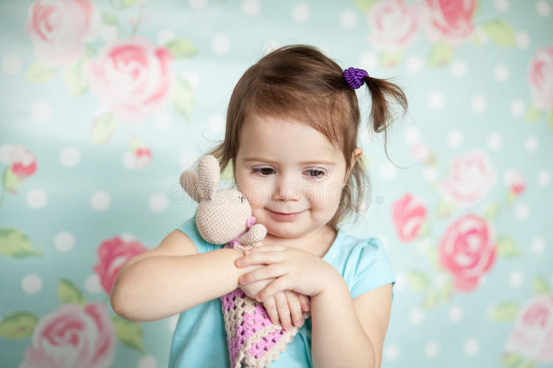 Little girl playing with her knitted toys stock image