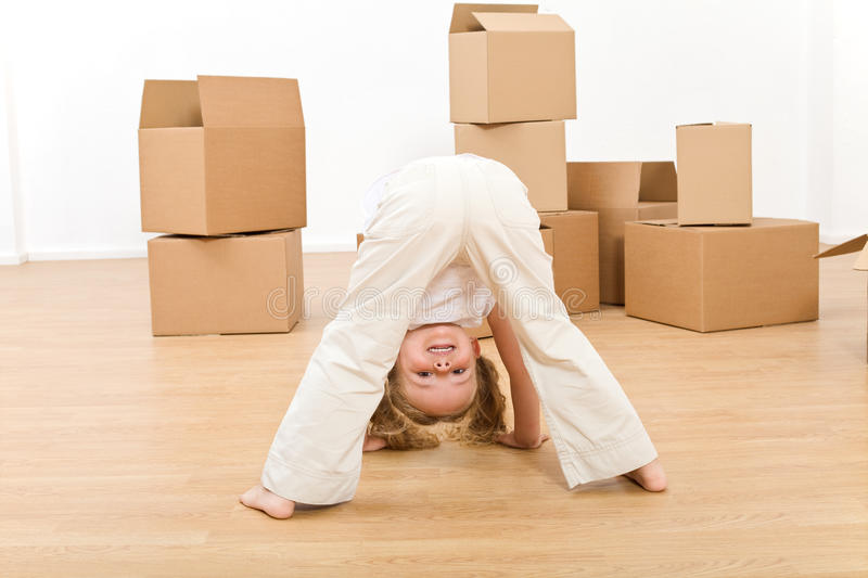 Little girl playing in her new home. Having fun among boxes royalty free stock photography