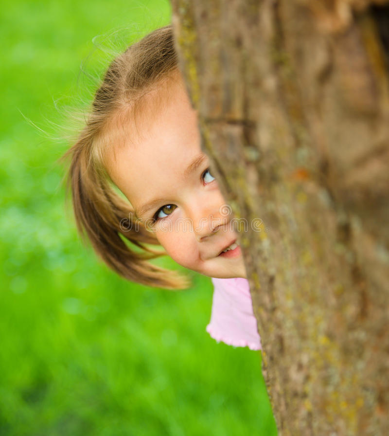 Little girl is playing hide and seek outdoors