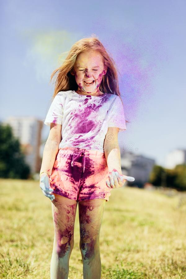 Little girl playing with holi powder outdoors royalty free stock images