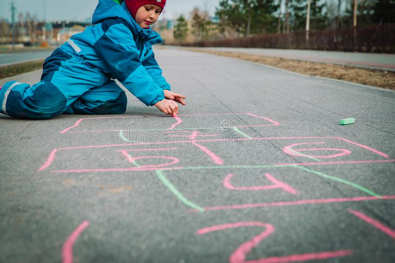 Little girl playing hopscotch on playground outdoors stock image