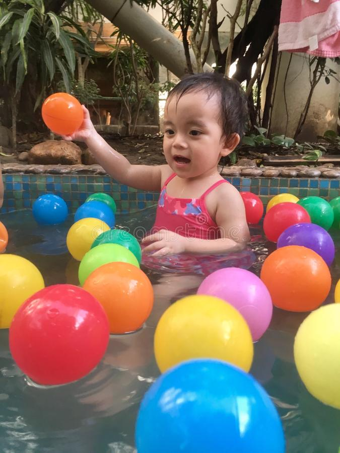 Little girl playing in hot spring pool. Baby surprised by lots of colorful balls in winter hot spring and having fun stock photos