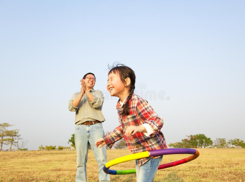 Little girl playing hula hoops outdoors. Happy little girl playing hula hoops outdoors stock photos